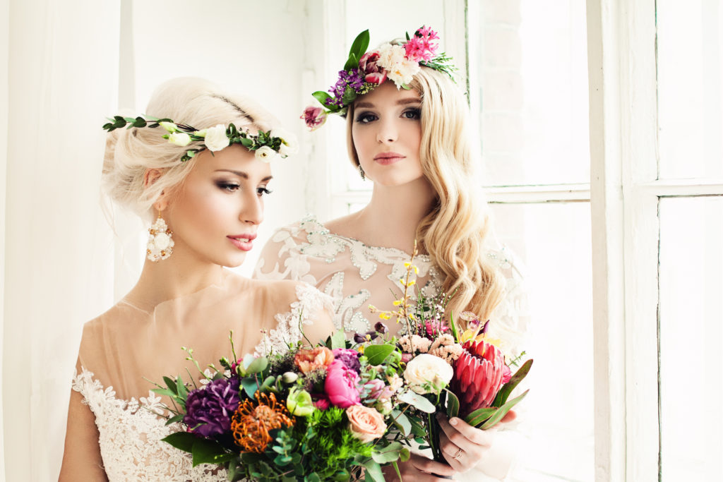 Beautiful Bride Woman with Colorful Flower Arrangement, Flower Wreath, Bridal Hairstyle and Makeup
