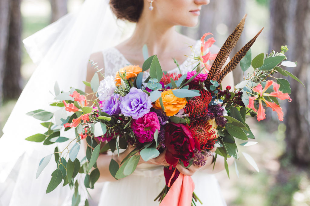Colorful bouquet in boho style in the bride's hands