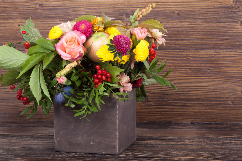 Amazing autumn bouquet with berries in a wooden vase on wooden background