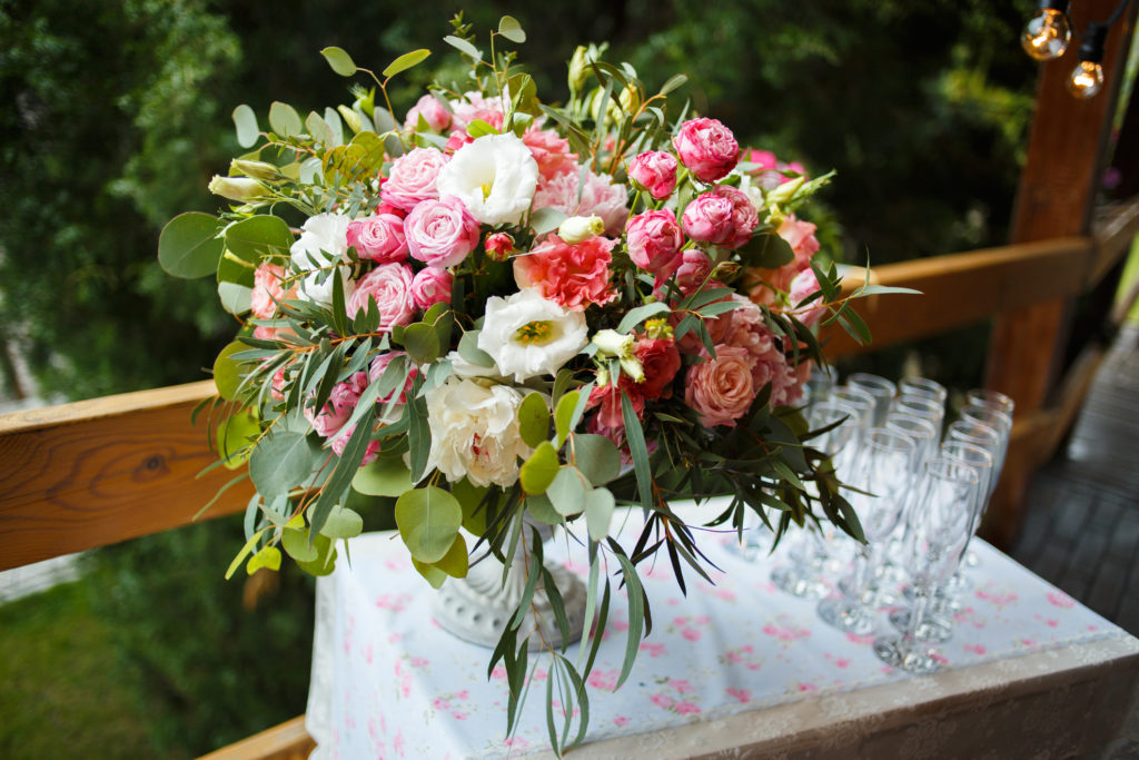 bright bouquet of peony on the wedding table with glasses on a green background